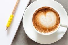 Kaffeetasse mit Notizblock auf grauem Hintergrund Stockfotografie