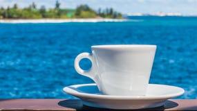 Kaffeetasse mit schönem Meerblickhintergrund Lizenzfreie Stockbilder