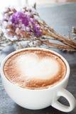 Kaffeetasse mit schöner violetter Blume Stockfotografie