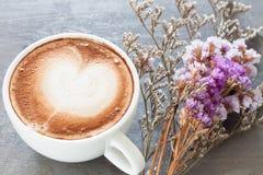 Kaffeetasse mit schöner violetter Blume Stockbild