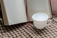 Kaffeetasse mit Schaum auf dem Hintergrund des Buches mit sauberen Seiten Lizenzfreies Stockbild