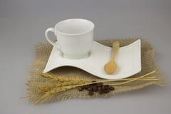 Kaffeetasse mit Teelöffel auf Juteleinwandtextilisolathintergrund Stockfotografie