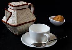 Kaffeetasse mit Topf auf schwarzem Hintergrund Stockbilder