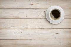 Kaffeetasse mit Untertasse auf hölzernen Planken Hintergrund, Draufsicht lizenzfreie stockfotos
