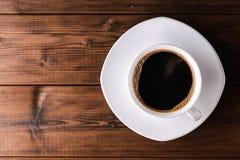 Kaffeetasse mit Untertasse auf Holztisch Lizenzfreies Stockfoto