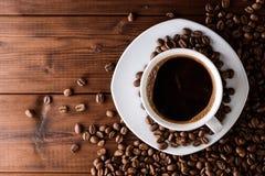 Kaffeetasse mit Untertasse und Bohnen auf Holztisch Lizenzfreie Stockfotografie