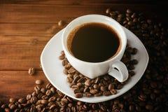 Kaffeetasse mit Untertasse und Bohnen auf Holztisch Stockfoto