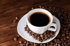 Kaffeetasse mit Untertasse und Bohnen auf Holztisch Stockfotos