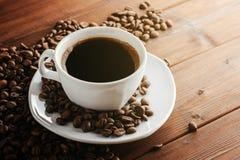 Kaffeetasse mit Untertasse und Bohnen auf Holztisch Lizenzfreie Stockfotos