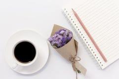 Kaffeetasse mit Veilchen des Blumenblumenstraußes auf weißer Tabelle Stockfotografie