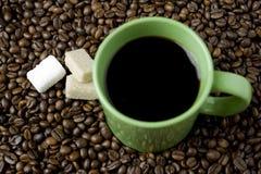 Kaffeetasse mit Zuckerwürfel und Kaffeebohnen Stockfotografie