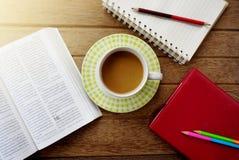 Kaffeetasse, Notizbuch, Bleistifte auf dunklem Holztisch Stockbild