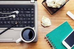 Kaffeetasse, Notizbuch, Kopfhörer, mobiler Smartphone und Laptop Stockbilder