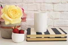 Kaffeetasse-Produkt-Anzeige Kaffeetasse auf gestreiften Design-Notizbüchern Erdbeeren in der Goldschüssel, Vase mit rosa Rosen Stockfotos