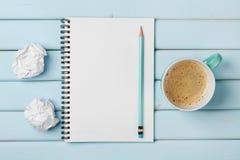 Kaffeetasse, sauberes Notizbuch, Bleistift und zerknittertes Papier auf blauer rustikaler Tabelle von oben, kreative Forschung un Stockbilder