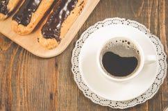 Kaffeetasse, Teekanne und Eclairs/Kaffeetasse, Teekanne und Eclairs auf einem hölzernen Hintergrund Beschneidungspfad eingeschlos lizenzfreie stockfotografie
