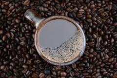 Kaffeetasse umgeben durch frische gebratene Bohnen Stockfotografie