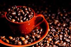 Kaffeetasse umgeben durch Kaffeebohnen Stockbild