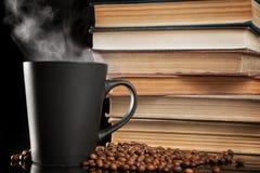 Kaffeetasse und alte Bücher auf Schwarzem Stockfoto