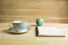 Kaffeetasse und Anmerkungsbuch auf Holztisch Stockbilder