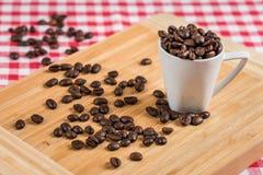 Kaffeetasse und Bohnen auf einer rustikalen Tabelle Stockfoto