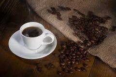 Kaffeetasse und Bohnen auf Holztisch Lizenzfreie Stockfotos