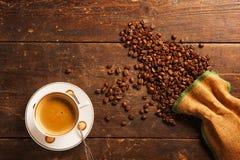 Kaffeetasse und Bohnen auf Holztisch Stockfoto