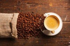 Kaffeetasse und Bohnen auf Holztisch Lizenzfreie Stockbilder