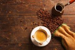 Kaffeetasse und Bohnen auf Holztisch Stockfotografie