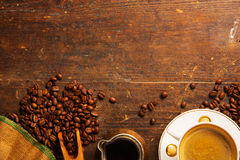 Kaffeetasse und Bohnen auf Holztisch Lizenzfreies Stockfoto