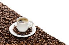 Kaffeetasse und Bohnen lokalisiert auf weißem Hintergrund Lizenzfreie Stockbilder