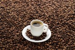 Kaffeetasse und Bohnen lokalisiert auf weißem Hintergrund Lizenzfreies Stockfoto