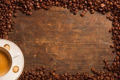 Kaffeetasse und Bohnenrahmen auf Holztisch Stockbilder