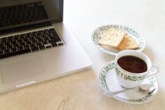 Kaffeetasse und Cracker mit Laptop auf Marmortabelle Lizenzfreies Stockbild