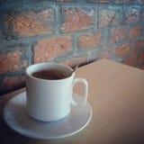 Kaffeetasse und die Backsteinmauer Stockfoto