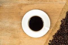 Kaffeetasse und gebratene Bohnen über grobem Sackzeug Stockbild