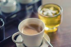 Kaffeetasse und grüner Tee auf Tabelle Lizenzfreies Stockbild