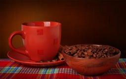 Kaffeetasse und Kaffeebohnen auf einer Tischdecke auf einem dunklen Hintergrund Lizenzfreie Stockbilder