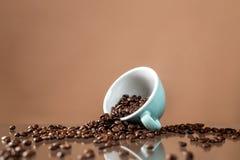 Kaffeetasse und Kaffeebohnen auf Farbhintergrund stockbilder
