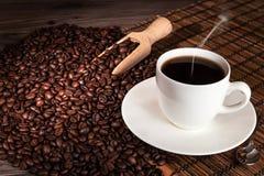 Kaffeetasse und Kaffeebohnen auf hölzernem Hintergrund Lizenzfreie Stockbilder