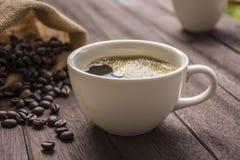 Kaffeetasse und Kaffeebohnen auf Holztisch Stockbild