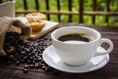 Kaffeetasse und Kaffeebohnen auf Holztisch Lizenzfreie Stockfotos