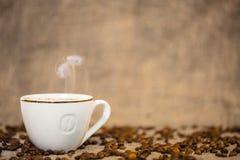 Kaffeetasse und Kaffeebohnen auf Tabelle Stockfotos