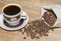 Kaffeetasse und Kaffeebohnen in der Tasche lizenzfreie stockfotografie