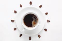 Kaffeetasse und Kaffeebohnen gegen den weißen Hintergrund, der die Uhrskala angesehen von der Spitze bildet Lizenzfreie Stockfotos
