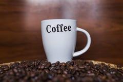 Kaffeetasse und Kaffeebohnen mit hölzernem Hintergrund Lizenzfreies Stockbild