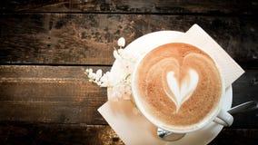 Kaffeetasse und kleine weiße Blume auf hölzerner Tabelle lizenzfreies stockfoto