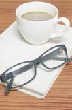 Kaffeetasse und Notizbuch mit Gläsern Lizenzfreie Stockfotografie