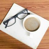Kaffeetasse und Notizbuch mit Gläsern Stockfotografie