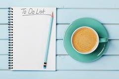 Kaffeetasse und Notizbuch mit, zum der Liste auf blauem rustikalem Schreibtisch von oben zu tun, planend und Konzept des Entwurfe Lizenzfreies Stockfoto